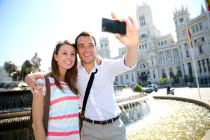 Couple taking pictures in Plaza de Cibeles, Madrid
